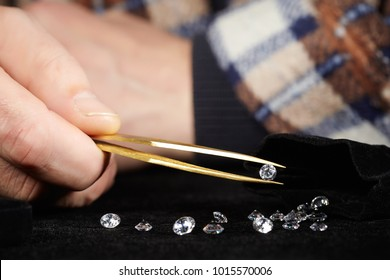 Old style diamond smuggler taking stones to tweezers