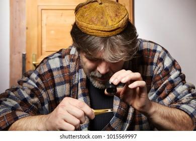 Old style diamond smuggler watching quality of diamonds
