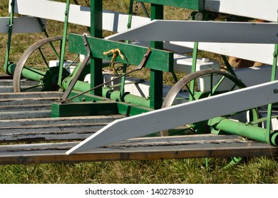 Old style hay rake is pushed by draft horses to mound the hay onto a beaver-slide lift.