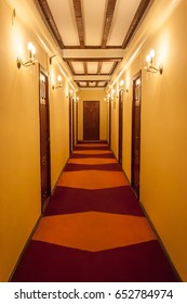 Old style hotel hallway with wooden brown doors, reddish carpet, and yellow walls.