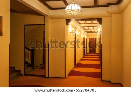 Old style hotel hallway with wooden brown doors, reddish carpet, and yellow walls. Mirror seen near the floor stairs.