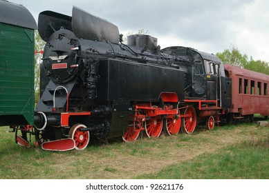 Old style locomotive with cars attached.