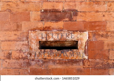 Old style mail slot. Lettere - telegrammi (letters - telegrams): vintage inner post box (mailbox) behind the front wall of a red brick historical building in Bologna, Italy.