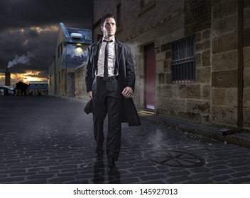 Old style man in factory area wearing a black suit and coat
