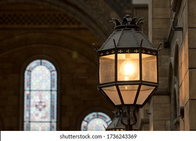 Old style metal and glass wall lamp in religious building. Retro light fitting on an interior wall. Olde worlde vintage light design with bright electric incandescent bulb glowing with warm light.