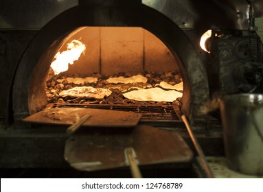 Old style middle east stone oven with flat bread with different spices inside