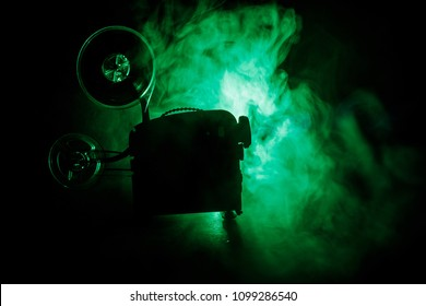 Old style movie projector, still-life, close-up. Film projector on a wooden background with dramatic lighting and selective focus. Movies and entertainment concept