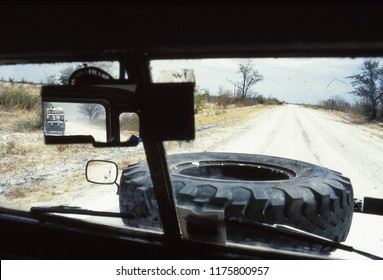 Old style photo looking threw the winscreen of a landrover in the African bush, with another landrover in the rear view mirror