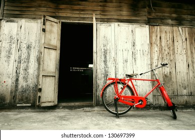 old style red bicycle and wooden door