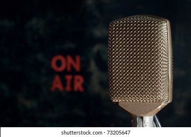 Old style retro microphone with on air sign and grunge background.