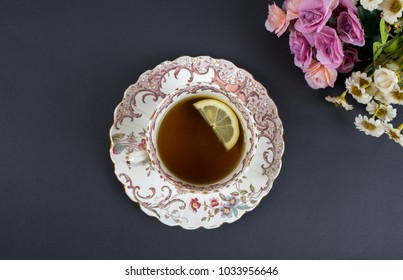 Old style rustic, vintage tea cup top view, with lemon and flowers