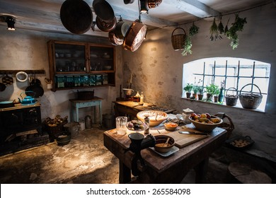 Old style vintage kitchen made of stone and clay, with wooden kitchen table and bronze pans and pottery.