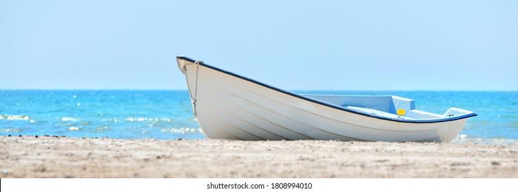 Old style (vintage) white rowboat on a sandy seashore, close-up. Idyllic summer scene. Transportation, nautical vessel, travel destinations, sport, recreation, hobby, vacations, leisure activity