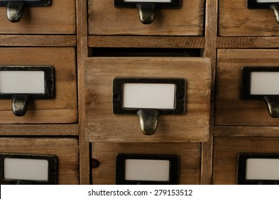 An old style wooden cabinet of library card index drawers with label holders and blank labels facing front.  One drawer in the middle is opened.