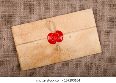 Old styled closed envelope with red sealing wax stamp, burlap background