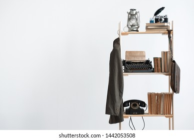 Old suit is hanging on a wooden rack with a kerosene lamp, stack of books, typewriter, photo camera and rotary phone on a shelf on a white wall background with copy space.