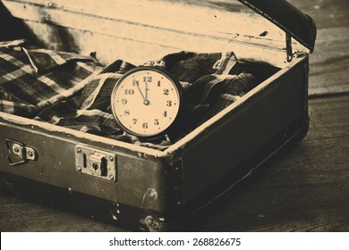 Old suitcase with old alarm clock and old shirt