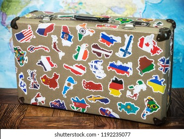 old suitcase with country flag stickers from traveling around the world on the floor. World map background
