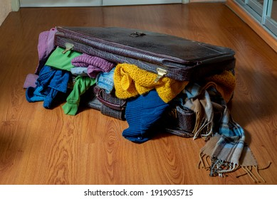 Old suitcase overflowing with used clothes on the floor. Sorting wardrobe and textiles. Sustainable life