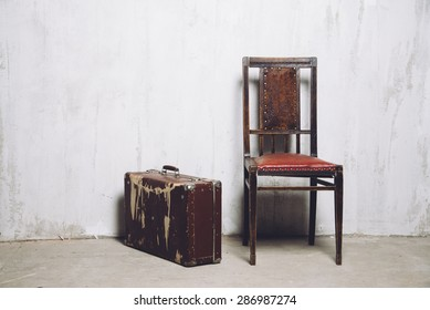 old suitcase and retro chair near old gray grunge wall. vintage concept with copy space.