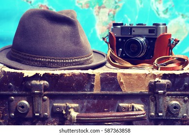 Old suitcase,camera,hat,map.Background travel.Photo toned in retro style.
