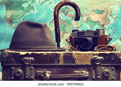 Old suitcase,camera,umbrella,hat,map.Background travel.Photo toned in retro style.