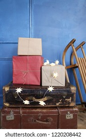 old suitecases, gift boxes and sleigh near the datk blue wall. Hello winter, December, January. February