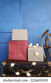 old suitecases, gift boxes and sleigh near the dark blue wall. Hello winter, December, January. February