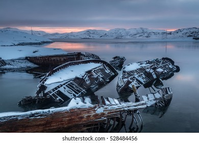 Old sunken fishing boats on the shore of the Barents Sea at sunrise. Teriberka. Russia