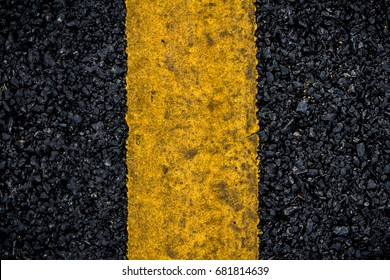 Old surface road, Top view of surface road, Closeup of an asphalt road texture with painted yellow line on the side for design and decorative