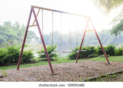 Old swing on the playground at river side with flare
