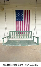 Old swing on porch displaying an American Flag and patriotic theme