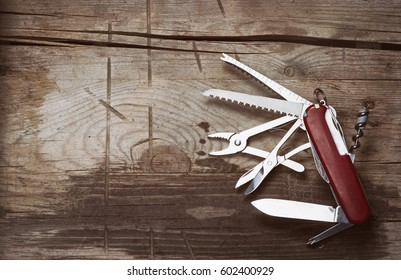 old Swiss knife on a wooden background. Top view with copy space