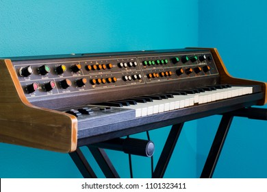 Old synthesizer with colorfull switches on blue background