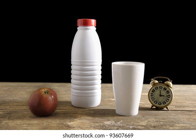 Old table with bottle of milk, cup, apple and old vintage clock on 4 o'clock