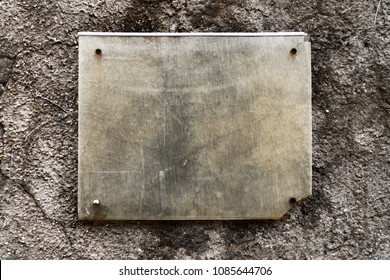An old tablet hanging on a stone wall, a sign for placing text, a beautiful texture