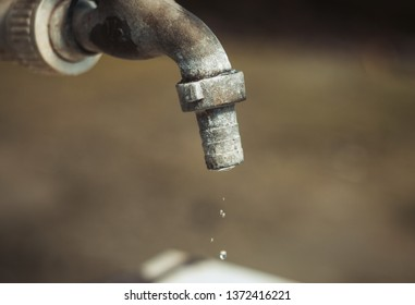 Old tap outdoors with the water drops