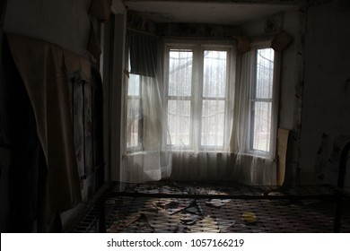 Old tattered floral lace sheer curtains in window of abandoned rural farm house
