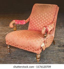 Old tattered red armchair on a wooden parquet