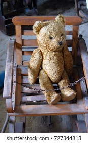old teddy bear in children's chair
