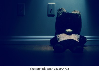 Old Teddy Bear sitting against wall at night. Faded look.