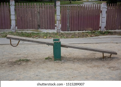 Old teeter-totter on an abandoned playground on the promenade in the city