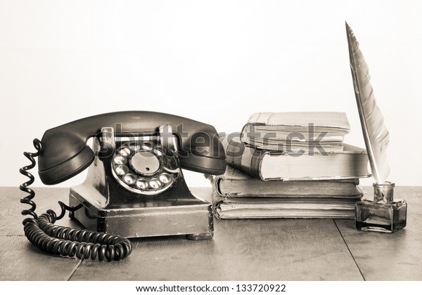 Old telephone, books, quill pen and inkwell on wooden table sepia photo