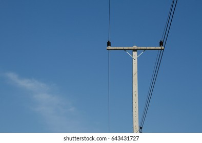 an old telephone Electricity pole for energy with power lines over a clear blue sky