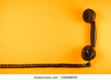 old telephone handset of the early twentieth century isolated with its elastic spiral cable on neutral color background