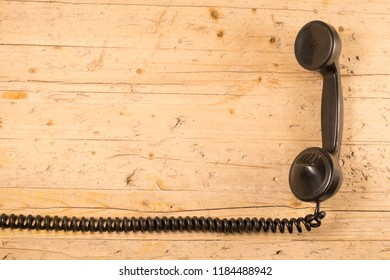 old telephone handset of the early twentieth century isolated with its elastic twisted cord on old wooden background