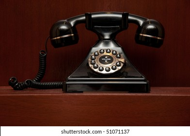 Old telephone on red wooden background. Copy space on the bottom.