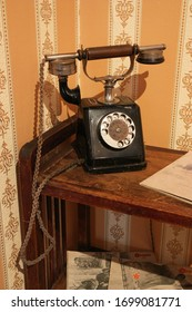 An old telephone on an old table with yellow Wallpaper.