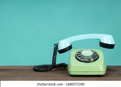 Old telephone on wooden table in front of green background. Vintage phone with taken off receiver. Vintage style photo.
