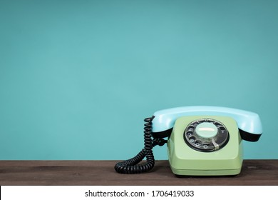Old telephone on wooden table in front of green background. Vintage phone